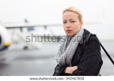 Casually dressed young stylish female traveller boarding airplane in cold winter weather wearing winter coat and wool scarf. Woman on Business travel. - stock photo