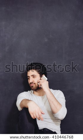Casually handsome. Handsome young arabic man holding cell phone while standing against grey background - stock photo