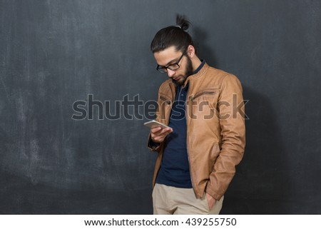 Casually handsome. Handsome young arabic man holding cell phone while standing against grey background