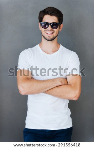Casually handsome. Handsome young man keeping arms crossed and smiling while standing against grey background - stock photo