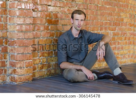 Casually handsome. Handsome young man sitting on the floor. his back against a wall of red brick. confident look - stock photo