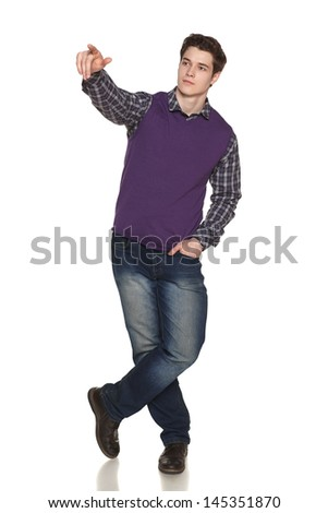 Casually standing young man in full length pointing at blank copy space over white background - stock photo