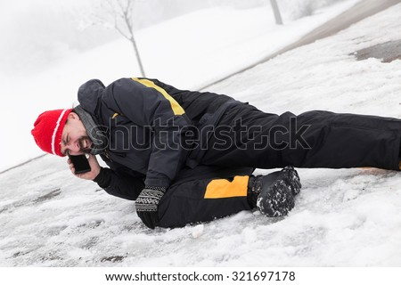 Casualty man on a icy street is calling the ambulance - stock photo