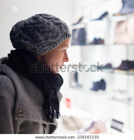 Casualy winter dressed lady window shopping in front of sinfully expensive boutique store dispaly window. Customer woman in shopping street, looking at window, outdoor.