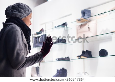 Casualy winter dressed lady window shopping in front of sinfully expensive boutique store dispaly window. Customer woman in shopping street, looking at window, outdoor. - stock photo