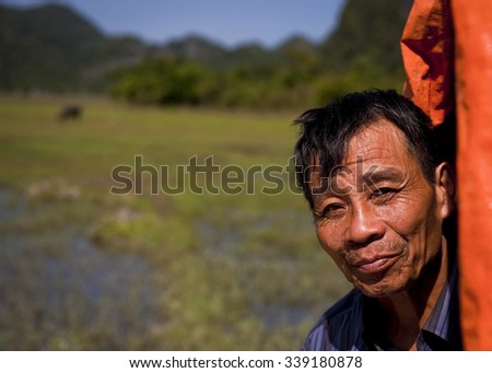 Cat Ba Island, Vietnam - November 3, 2015:  A local villager looks at viewer in front of his rice paddy and water buffalo in distance on Cat Ba Island, Vietnam