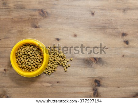 Cat food in bowl on wood background - stock photo