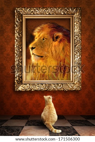 Cat looking at a portrait of a lion in a golden frame.   - stock photo
