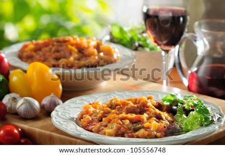 Catalan (Spanish) piquant chicken casserole dish with chorizo and hot peppers, served with a mixed lettuce salad. - stock photo