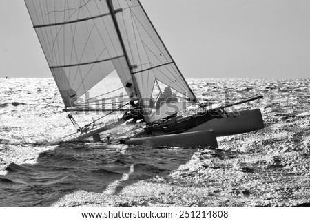 Catamaran going upwind on one hull shoot against the light and in black and white. - stock photo