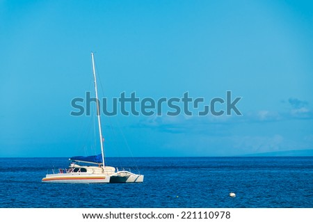 Catamaran on a sunny blue day moored in the Pacific Ocean off the island of Maui, Hawaii, USA - stock photo