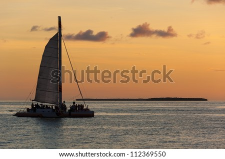 Catamaran sailing with tourists with a caribbean island behind at sunset. - stock photo