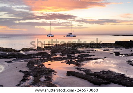 Catamarans at sunset offshore from Cabbage Tree Beach, Jervis Bay NSW Australia.  Feeling like a castaway on a deserted beach - stock photo