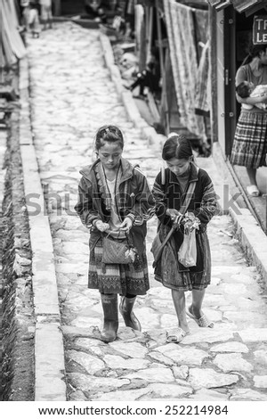 CATCAT, VIETMAN - SEP 20, 2014: Unidentified Hmong two sisters in traditional clothes walk in CatCat village, Vietnam. Hmong is a minority ethnic group of Vietnam