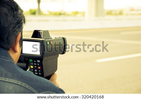 catch speeding drivers with a radar gun, vintage color style - stock photo