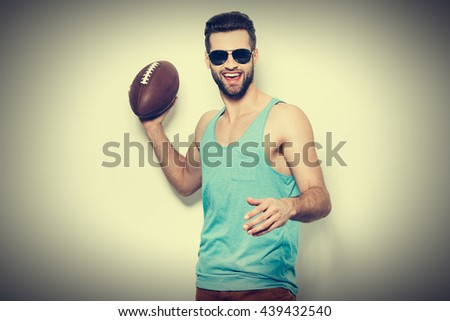 Catch the ball! Handsome young man in sunglasses holding American football ball and smiling while standing against white background  - stock photo