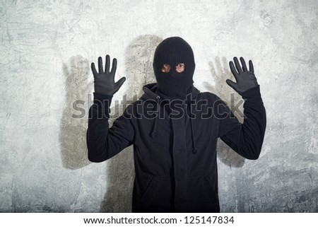 Catch the burglar concept, thief with balaclava caught in front of the grunge concrete wall. - stock photo