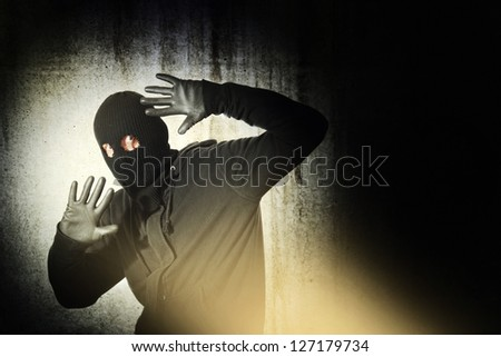 Catch the burglar concept, thief with balaclava caught in front of the grunge concrete wall.