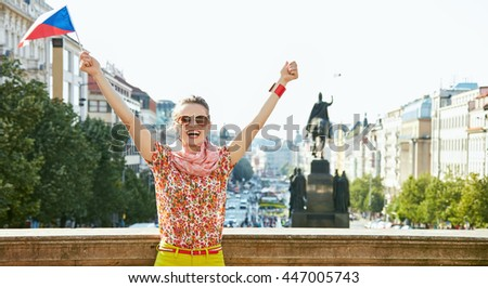 Catch the spirit of old Europe in Prague. Happy young woman in sunglasses with Czech flag standing near National Museum at Wenceslas Square and rejoicing