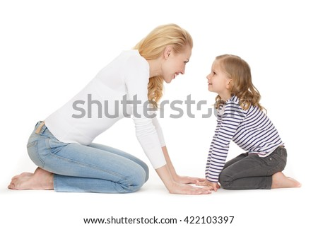 Catch this moment. Studio shot of an adorable mature woman sitting on her knees in front of her daughter nose to nose smiling on white background.