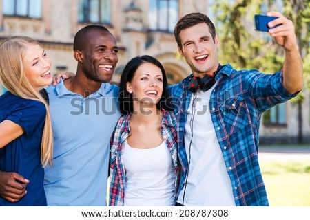Catching a moment from student life. Four happy young people making selfie while standing close to each other outdoors - stock photo