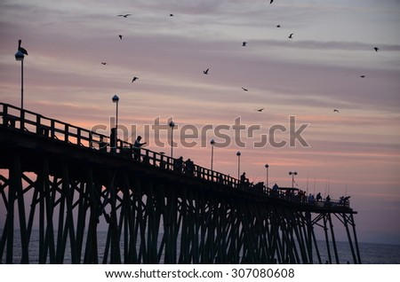 Catching fish off the pier. Sunrise at Kure Beach North Carolina on a warm summer morning.
