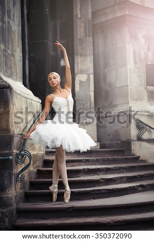 Catching last sun beams. Portrait of a ballerina performing outdoors near an old building  - stock photo