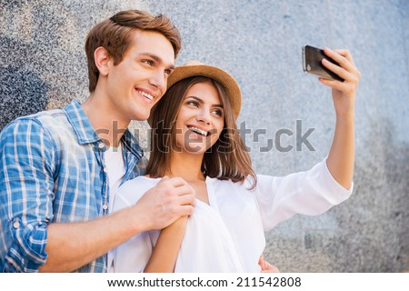 Catching the bright life moments. Beautiful young loving couple making selfie with smart phone and smiling while leaning at the wall - stock photo