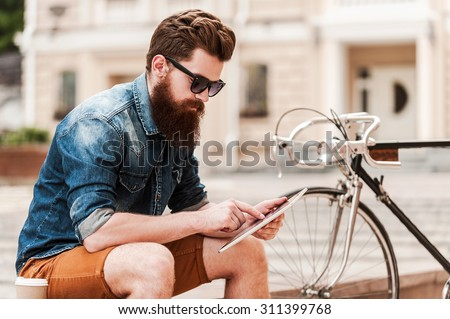 Catching up on some news. Handsome young bearded man holding digital tabletwhile sitting near his bicycle outdoors  - stock photo