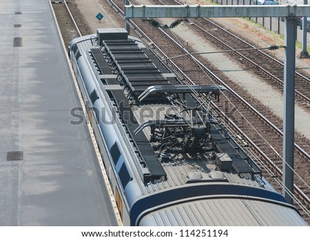 Catenary and departing train from above - stock photo