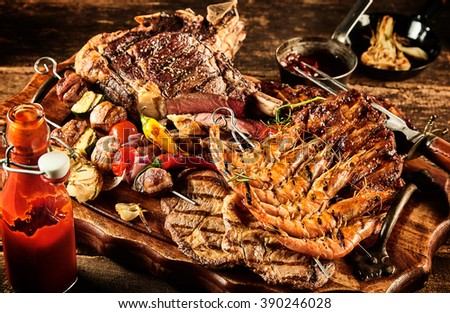 Catered barbecue beef, shrimp and skewered vegetables served on table with oil, ketchup and seasonings - stock photo