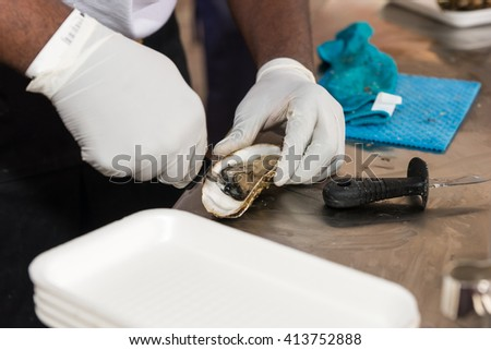 Caterer shucking a marine oyster with a shucking knife as he prepares it for eating at the table - stock photo