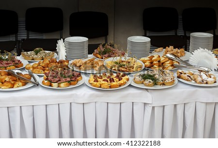 Catering banquet table with baked food snacks, sandwiches, cakes, cups and plates, self serve, open buffet dinner, horizontal view - stock photo