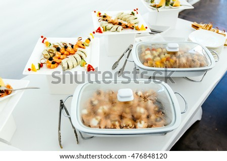 Catering food wedding, white beautiful table. Shrimp, kebabs rolls