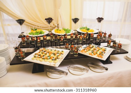 Catering for party. Close up of sandwiches, appetizers and fruit. Canape - stock photo