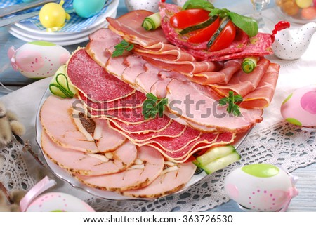 catering platter of sliced cured meat,ham and salami with vegetable decoration on easter table  - stock photo