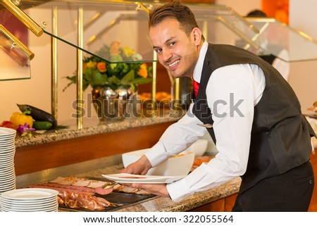 Catering service employees filling buffet at a restaurant or hotel - stock photo