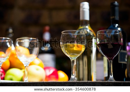 Catering service with white wine glass, fruits and wine buttles on bartender background