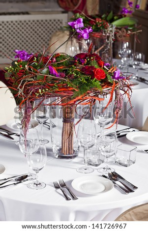 catering table set service with silverware, fresh flowers and glass at restaurant before party