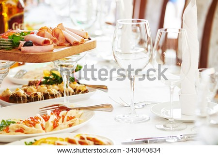 catering table set service with silverware, napkin and glass stemware at restaurant before party - stock photo