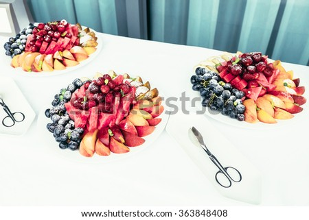 catering with Assortment of juicy fruits on plates on white  table - stock photo