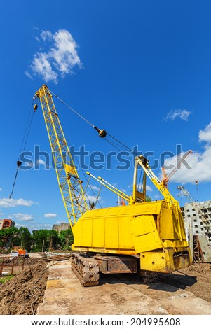 Caterpillar crane on the construction site beneath blue cloudy sky - stock photo