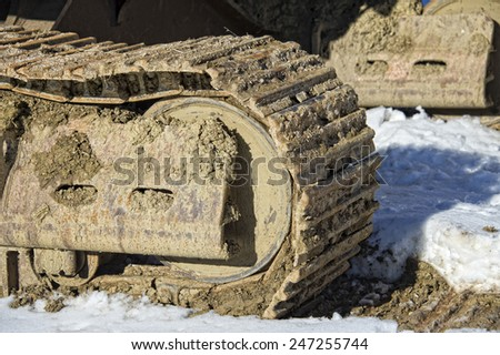 caterpillar track detail on snow background - stock photo