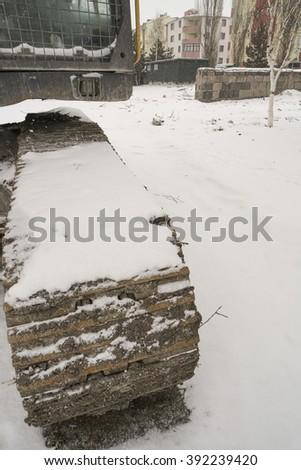 caterpillar wheel under snow winter - stock photo