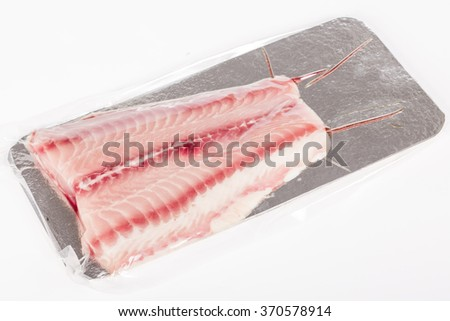 Catfish fillet on white background. Raw white catfish in silver plastic box packaging - stock photo