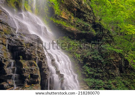 Cathedral Falls, a waterfall in West Virginia's scenic New River Gorge is viewed from alongside in late summer. - stock photo