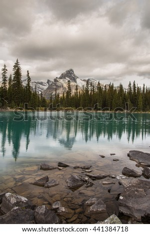 Cathedral Mountain on a cloudy day with reflection in Lake O'Hara, Yoho National Park, British Columbia, Canada