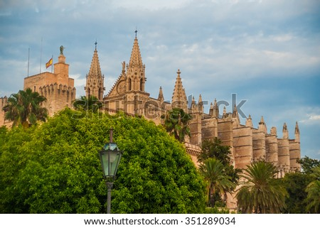Cathedral of Palma de Mallorca viewed through lush greenery of the island. Big gothic church beside palm trees under the blue sky at sunset. Beautiful travel picture of Spain. - stock photo