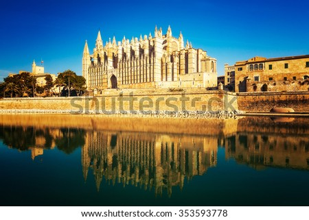 Cathedral of Palma de Mallorca with palm trees and water reflections against blue sky. La Seu gothic church at morning. Travel destinations - stock photo