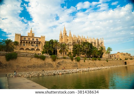 Cathedral of Palma de Mallorca with plam trees and water reflections of the pool against blue cloudy sky. Big gothic church on the sea shore. Beautiful travel picture of Spain. - stock photo